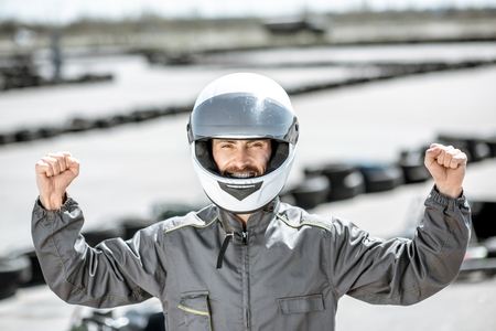 Portrait of a happy racer in protective sportswear standing as a winner of a go-kart race outdoors