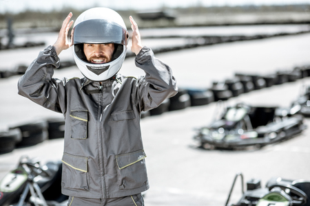 Portrait of a happy male racer in uniform wearing protective helmet while standing on the track with go-karts outdoors