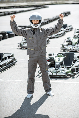 Full body portrait of a happy racer in protective sportswear standing as a winner of a go-kart race outdoors