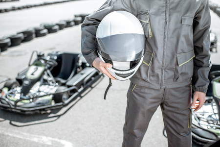 Racer holding protective helmet on the track with go-kart on the background