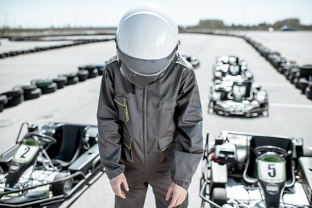 Despair racer in sportswear feeling sad standing as a loser on the go-kart track outdoors
