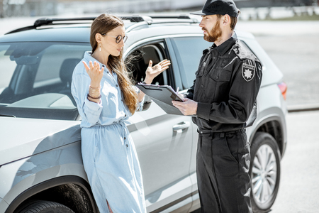 Policeman arguing with female driver while issuing fine for violating the traffic rules on the roadside near the car Stockfoto