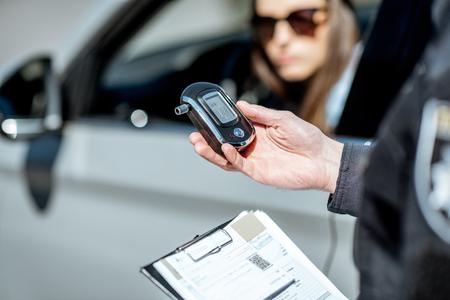 Poliziotto che tiene il dispositivo per controllare l'intossicazione da alcol mentre si trova vicino all'auto ferma con autista donna