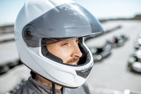 Close-up portrait of a male racer in protective helmet standing on the go-kart track outdoors