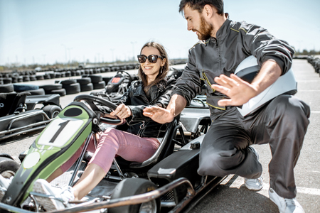 Man in sportswear instructing young woman driver before racing on the go-karts on the track outdoors