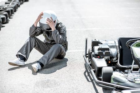 Despair racer in sportswear feeling sad lying on the track near the kart as a loser outdoors Stockfoto