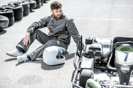 Despair racer in sportswear feeling sad lying on the track near the kart as a loser outdoors Stock Photo