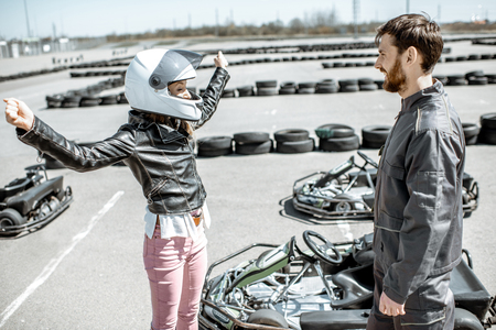 Happy female driver with instructor on the go-kart track outdoors