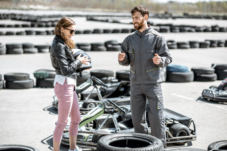 Male instructor in sportswear talking with young woman driver standing on the track with go-karts outdoors Stock Photo