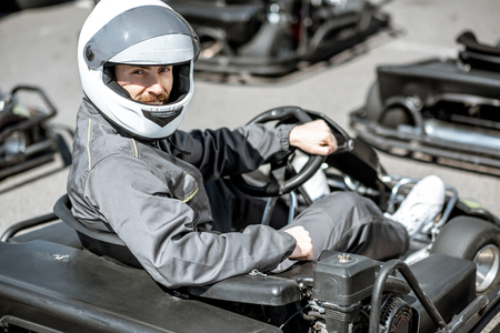 Portrait of a male racer in sportswear and protecive helmet sitting in the go-kart on the track outdoors Stock Photo