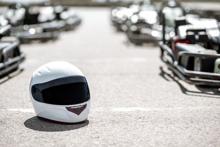 Protective helmet on the open track with karts on the background