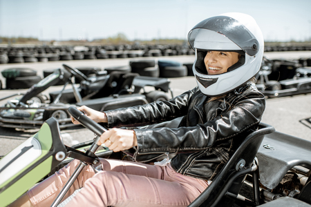 Young woman in protective helmet driving on the go-kart at the track outdoors Stockfoto