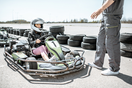 Man instructing young woman driver, explaining the rules before racing on the go-karts on the track outdoors