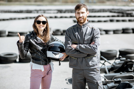 Happy instructor in sportswear with young woman driver on the go-kart track outdoors Stock Photo