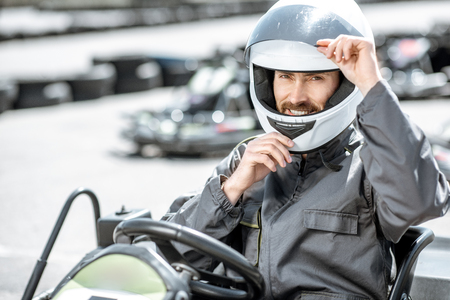 Portrait of a professional racer in sportswear and helmet sitting in the kart on the track Stock Photo