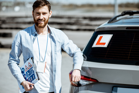Portrait of a handsome drivers instructor standing with road signs near the learning car on the training ground outdoors Stockfoto - 123768969