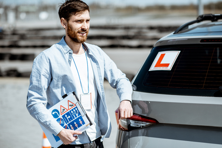 Portrait of a handsome drivers instructor standing with road signs near the learning car on the training ground outdoors Stockfoto - 123768970