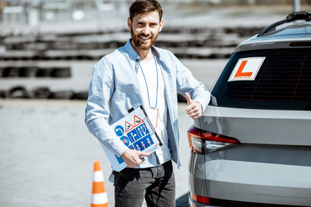 Portrait of a handsome drivers instructor standing with road signs near the learning car on the training ground outdoors