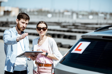 Male instructor showing road schemes for a female student, standing together near the learning car on the training ground outdoors