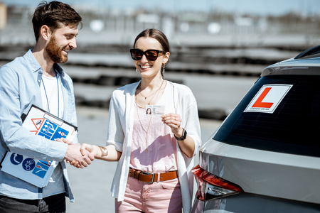 Instructor shaking hands with happy woman getting a drivers license while standing together on the training ground outdoors Stockfoto