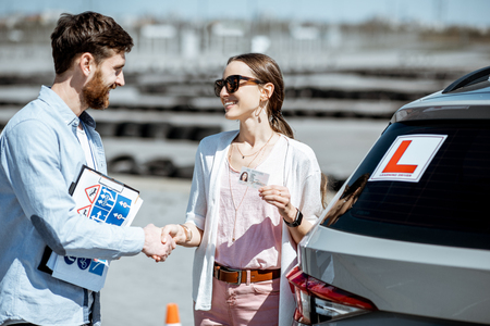 Instructor shaking hands with happy woman getting a drivers license while standing together on the training ground outdoors Stock fotó