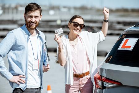 Ausbilder mit glücklicher Frau, die einen Führerschein macht, während sie zusammen auf dem Trainingsgelände im Freien steht Standard-Bild