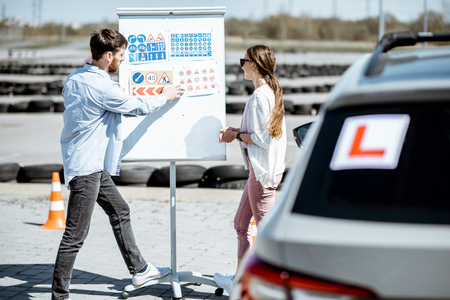 Male instructor showing traffic signs to a young female student standing on the training ground at the drivers school