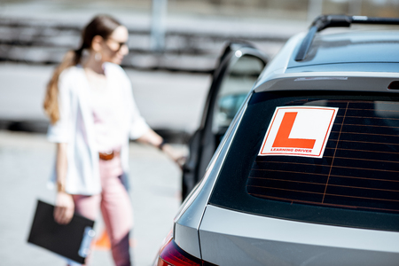 Learning sign on the car with woman driver on the background at the driving school outdoors Banco de Imagens