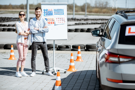 Portrait of an instructor and female student standing with road signs and learning car on the training ground at the drivers school 스톡 콘텐츠