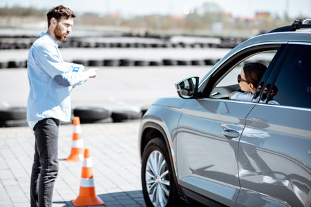 Male instructor teaching young woman driver to park a car on the training ground with traffic cones at the school Banque d'images