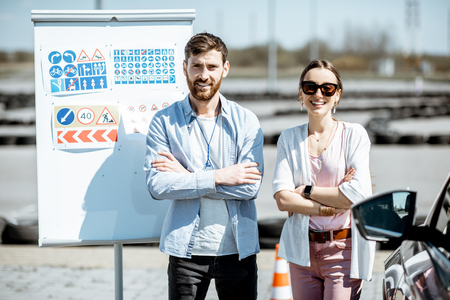Portrait of an instructor and female student standing with road signs and learning car on the training ground at the drivers school Stockfoto