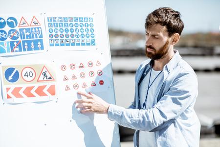 Männlicher Instruktor, der Verkehrszeichen auf einem Flipchart zeigt, der auf dem Trainingsgelände der Fahrerschule steht Standard-Bild