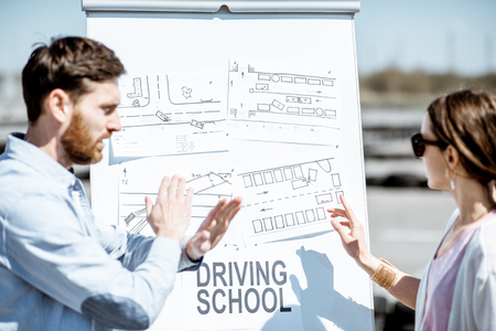 Male instructor showing traffic shemes to a young female student standing on the training ground at the drivers school