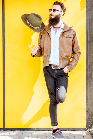Full length portrait of a stylish bearded man dressed in jacket and hat on the bright yellow background outdoors