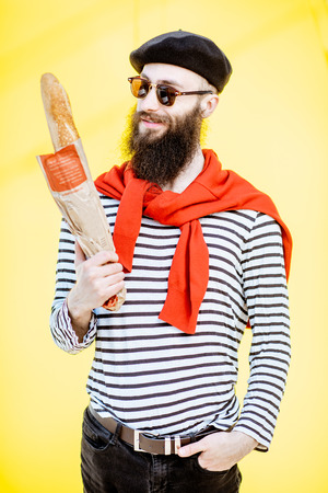 Portrait of a stylish man dressed in french style with striped shirt, hat and red scarf on the yellow background