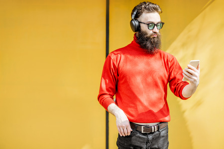 Portrait of a stylish man dressed in red sweater enjoying music with headphones and smart phone on the bright yellow background