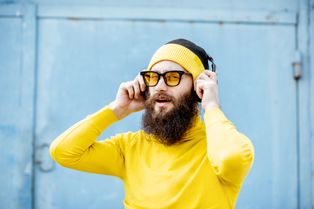 Portrait of a stylish bearded man in yellow clothes enjoying music with headphones on the blue background