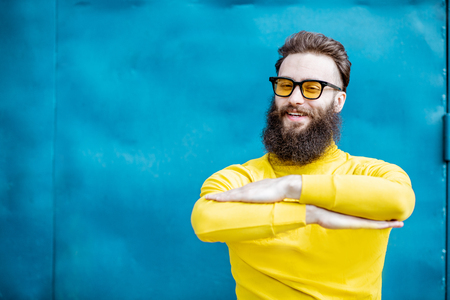 Portrait of a stylish bearded man in yellow sweater and sunglasses like a student on the blue background