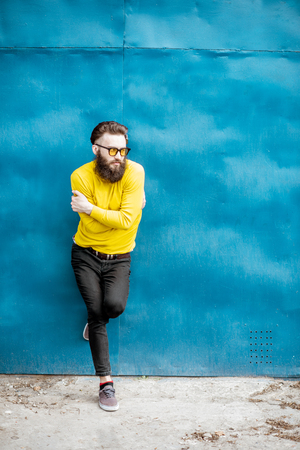 Full body portrait of a stylish bearded man in yellow sweater posing on the blue metal wall background Stockfoto