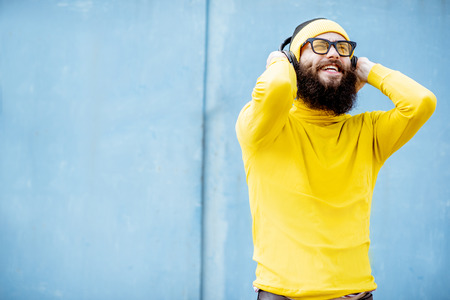 Portrait of a stylish bearded man in yellow clothes enjoying music with headphones on the blue background Zdjęcie Seryjne