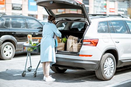 Vrouw verpakt voedsel gekocht in de supermarkt in de kofferbak op de parkeerplaats
