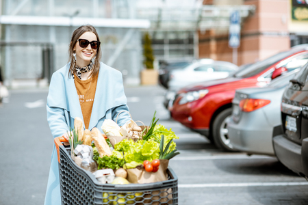Young woman with shopping cart full of fresh and healthy food on the parking place near the supermarket