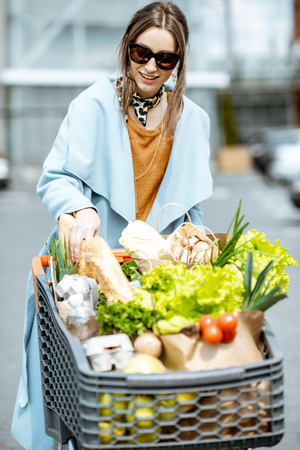 Young woman with shopping cart full of fresh and healthy food on the parking place near the supermarket Stock Photo
