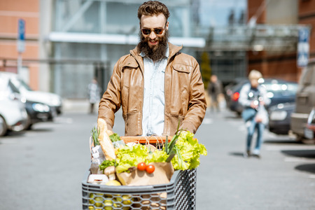 Stylish man with shopping cart full of fresh and healthy food on the outdoor parking near the supermarket 스톡 콘텐츠