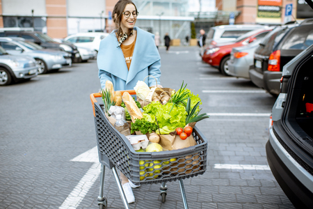 Young woman with shopping cart full of fresh and healthy food on the parking place near the supermarket Foto de archivo - 122230231