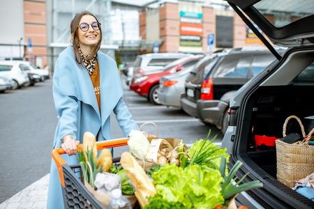 Mujer joven con carrito de compras lleno de comida fresca y saludable en el lugar de estacionamiento cerca del supermercado