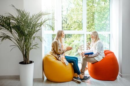 사무실에서 심리 상담을 하는 동안 편안한 의자에 앉아 있는 고위 여성 심리학자나 정신 코치를 둔 젊은 여성 스톡 콘텐츠