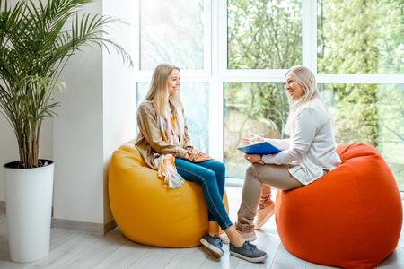 Jonge vrouw met senior vrouwelijke psycholoog of mentale coach zittend op de comfortabele stoelen tijdens de psychologische begeleiding op kantoor