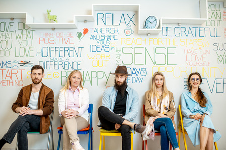 Group of diverse people sitting in a row on the wall background with various inscriptions on the topic of mental health indoors