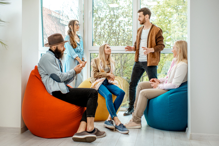 Group of diverse people having a conversation during the coffee break sitting on the colorful poufs near the window in the office 版權商用圖片